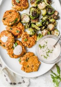 salmon cakes on a large plate with Brussels sprouts