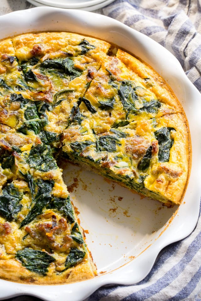 spinach quiche in a white pie plate with one slice taken out