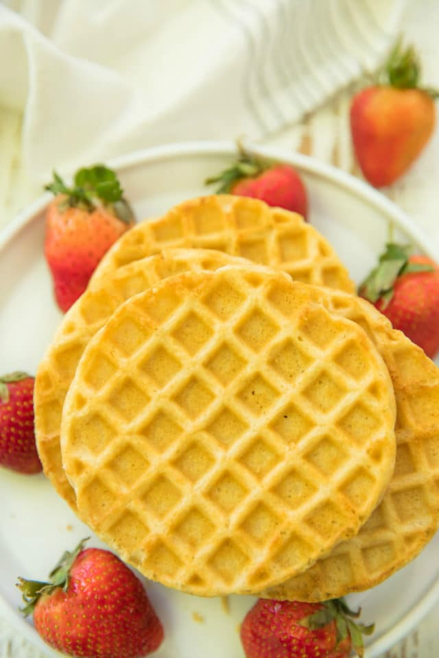 stack of frozen waffles on a white plate near fresh strawberries