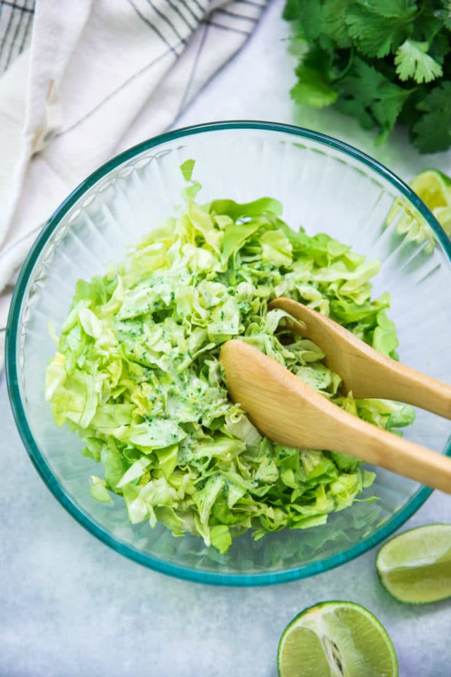 making cilantro lime slaw in a glass bowl with salad tongs