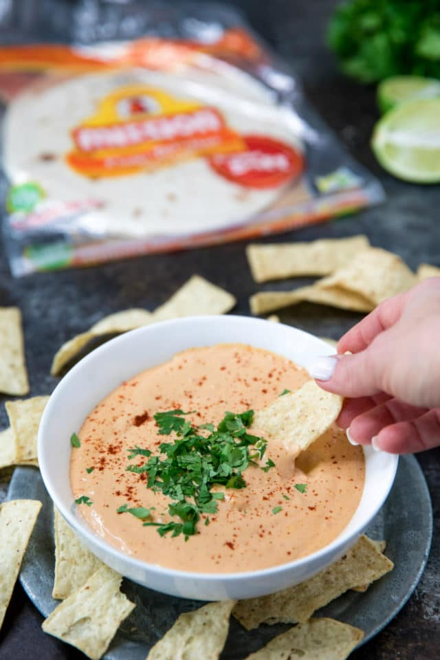 woman's hand dipping chip into dip