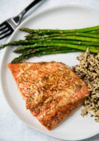 Honey Chipotle Salmon on a white plate served with asparagus and rice