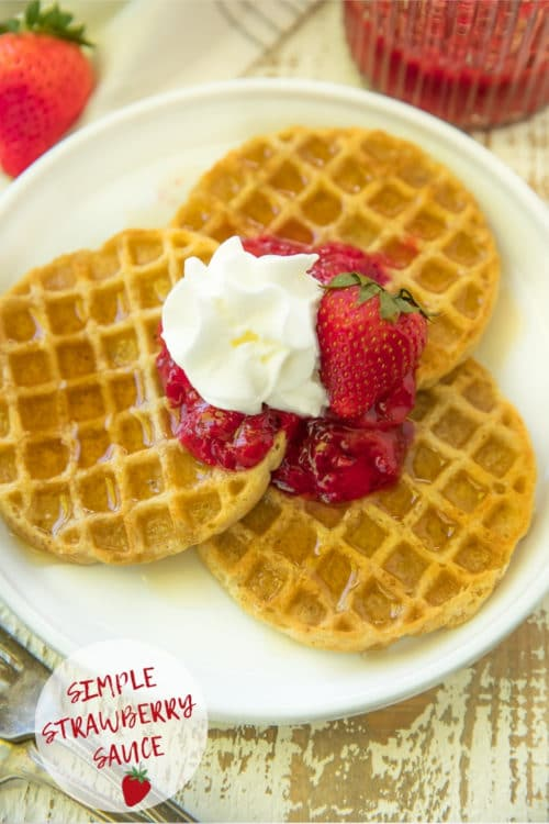 waffles served on a white plate with strawberry sauce and whipped cream