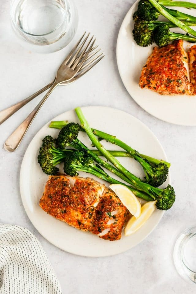 baked cod served with broccoli on a white plate