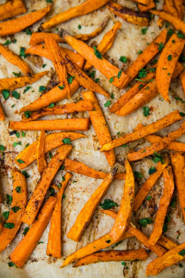 Crispy Baked Sweet Potato Fries on a baking sheet topped with chopped fresh parsley