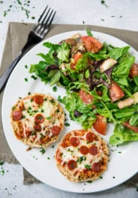 Mini Pepperoni Pizzas on a white plate with a side salad