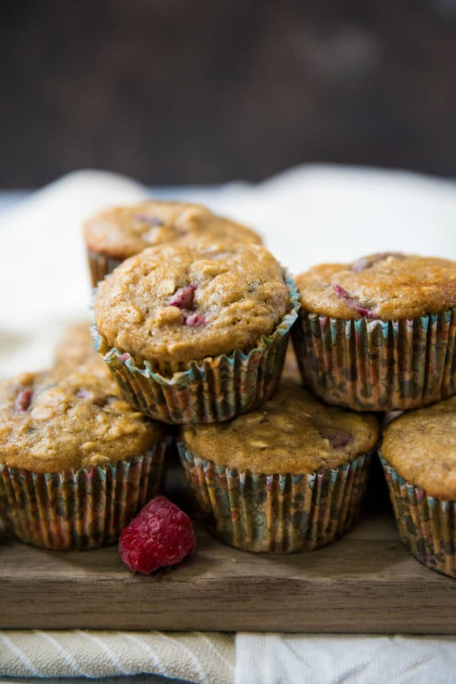 raspberry oatmeal muffins stacked on a wooden cutting board