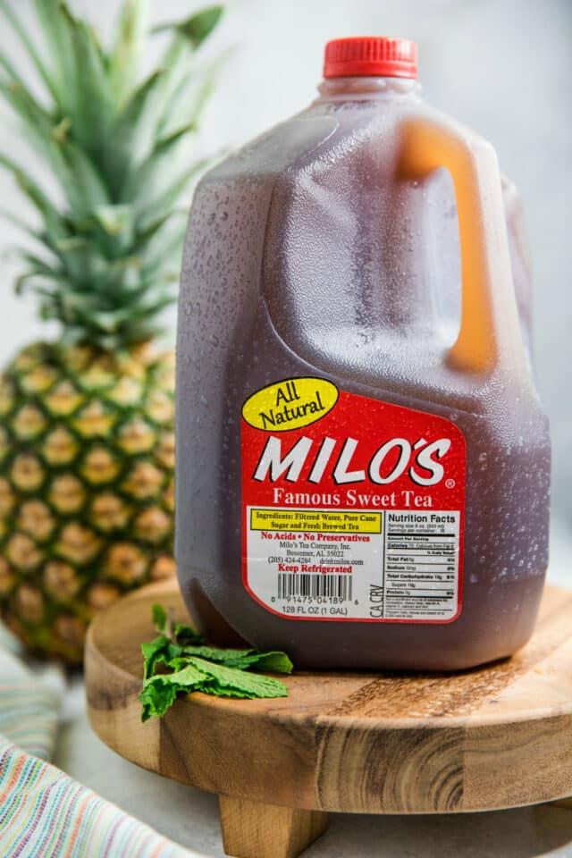 gallon jug of Milo's Sweet Tea near a pineapple