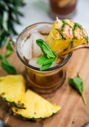 glass of iced tea with sprigs of mint and pineapple chunks