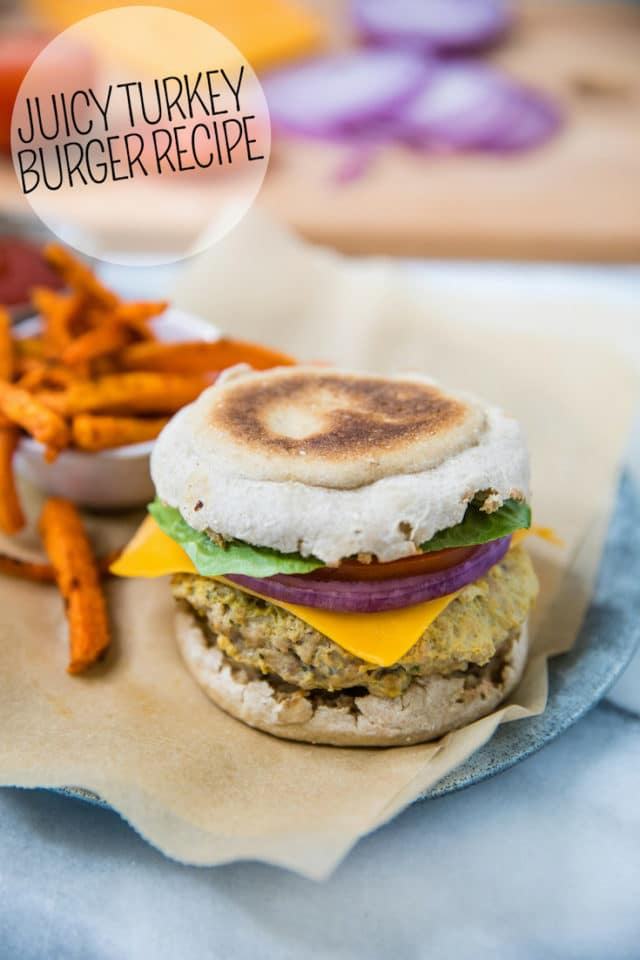 cheese burger with onion, tomato and lettuce served on an English muffin