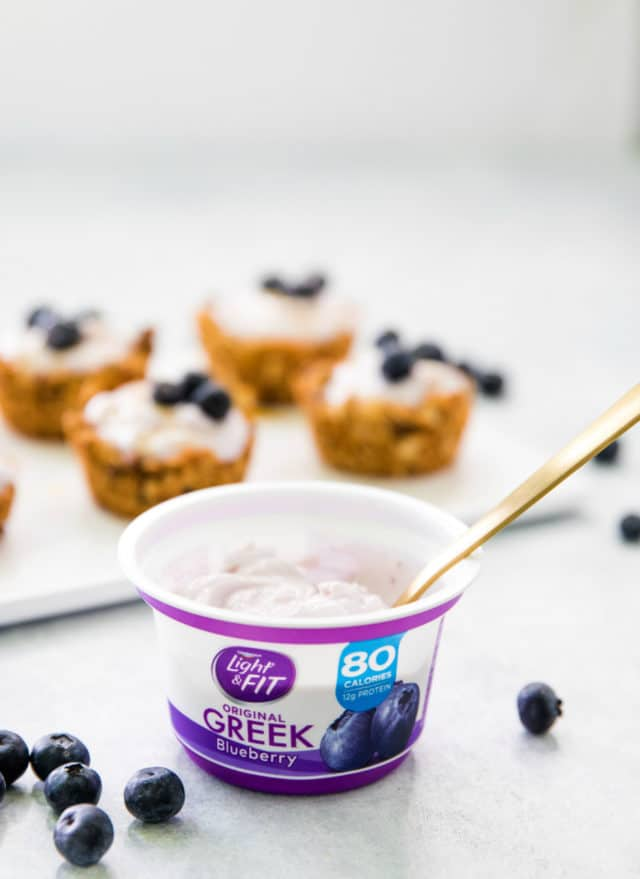 a gold spoon inside a cup of Dannon Light & Fit Greek Yogurt