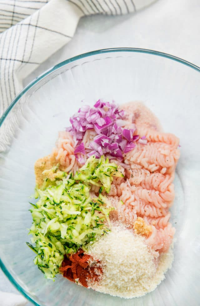 ingredients for zucchini turkey burgers in a large glass mixing bowl
