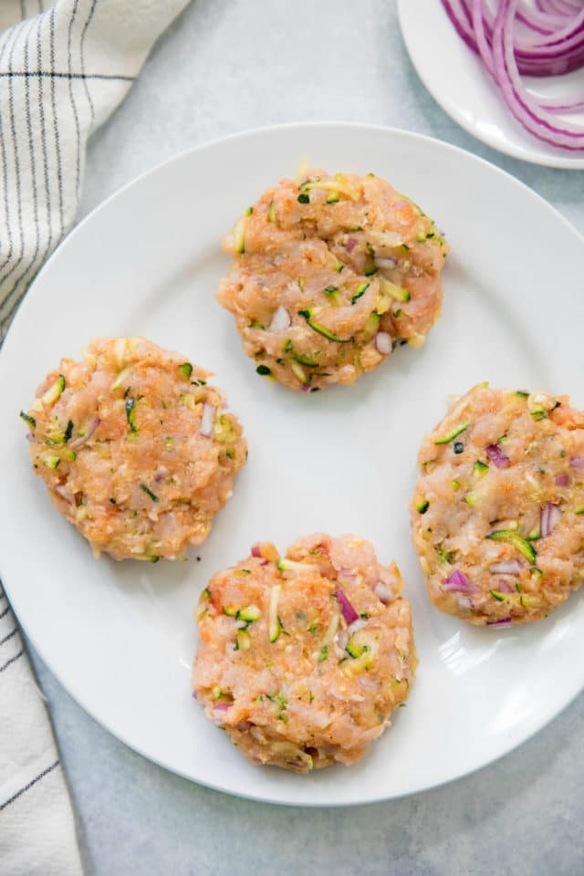 raw Zucchini Turkey Burger patties on a white plate