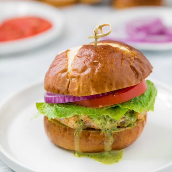 turkey burger with a pretzel bun topped with lettuce, tomato, red onion