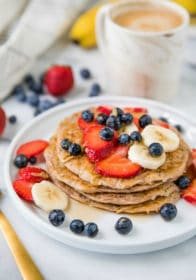 Protein Zucchini Pancakes stacked on a white plate and topped with berries
