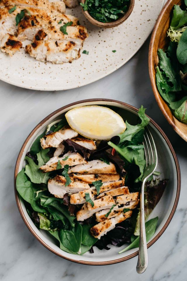 grilled chicken sliced and served on a bed of greens with a lemon wedge