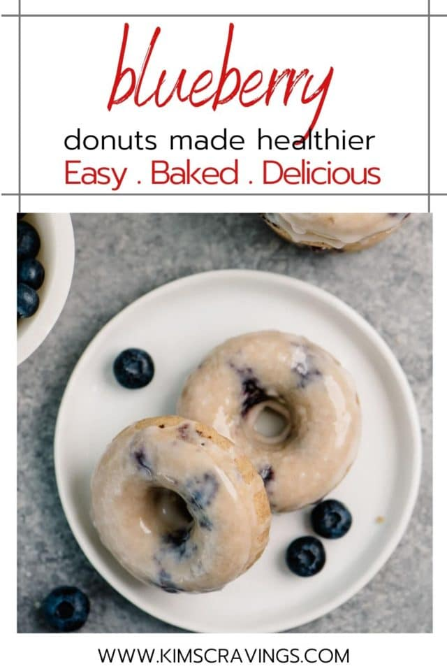 2 blueberry donuts on a white plate with fresh blueberries