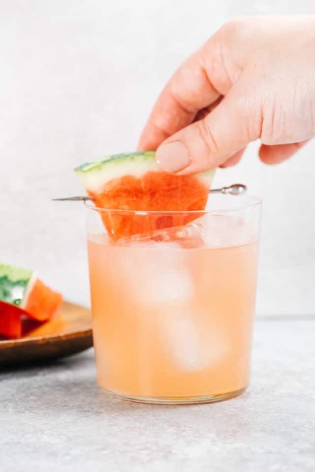 woman's hand garnishing watermelon cocktail with a wedge of fresh watermelon