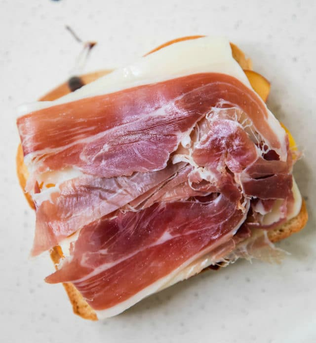 sliced bread topped with cheese and thinly sliced ham