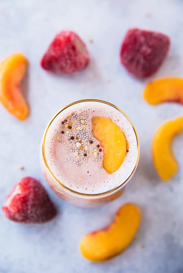 Strawberry Peach Protein Smoothie topped with a frozen peach