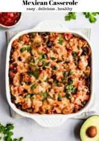 Mexican casserole in a white baking dish served with salsa and avocado