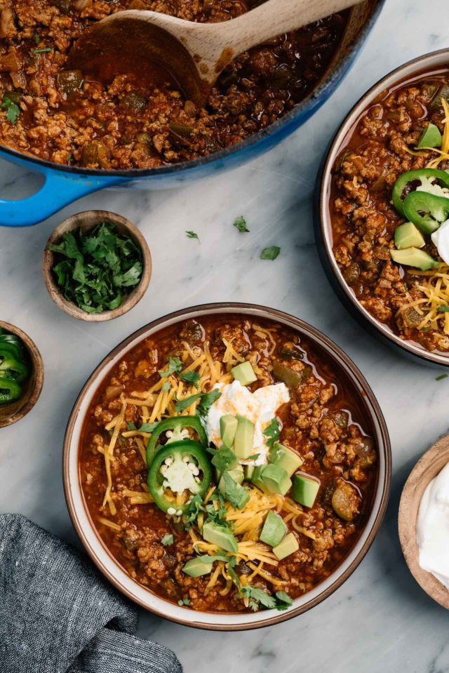 chili served in bowls with cheese, sour cream and avocado