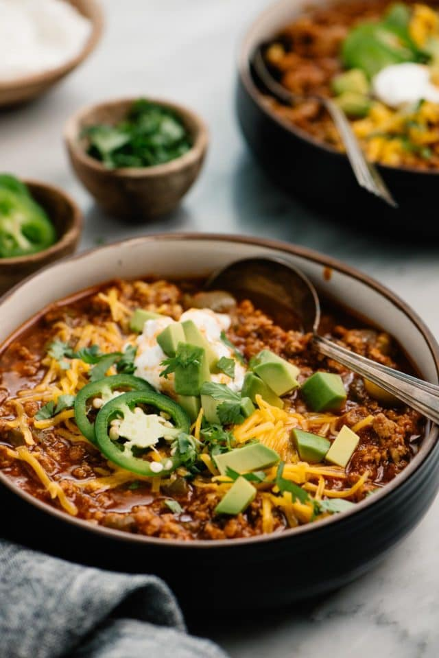 chili served in a bowl with a spoon and topped with cheese, sour cream, avocado and fresh cilantro