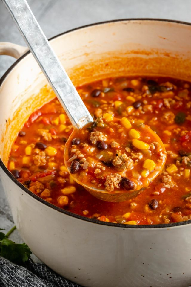 ladeling out a serving of taco soup from a large pot