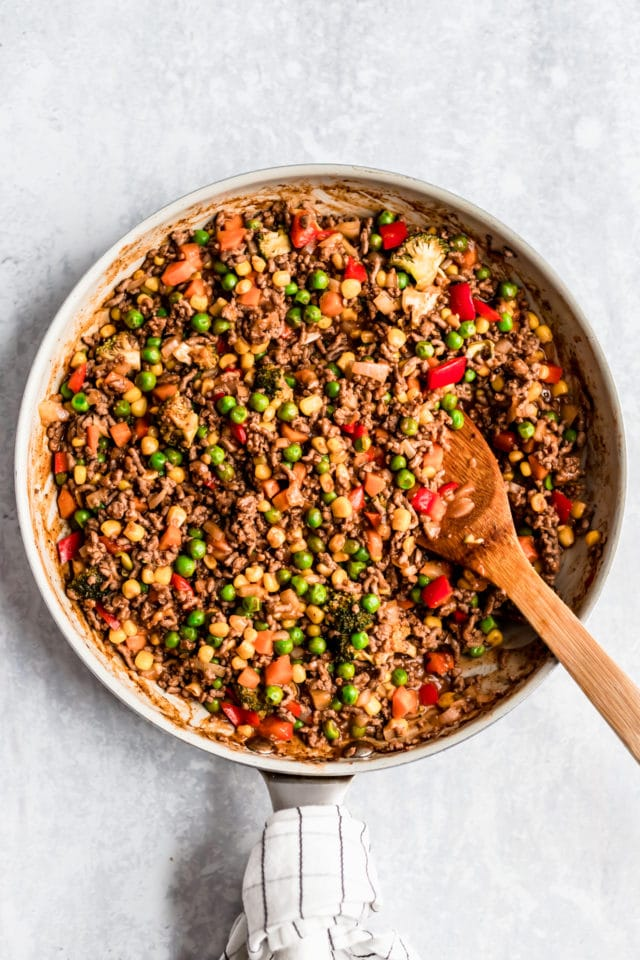 ground beef and veggies in a large skillet being stirred by a wooden spoon