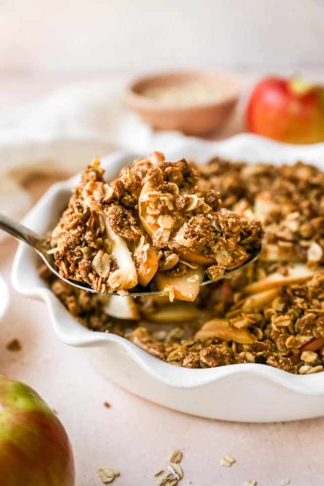 using a serving spoon to dish out a serving of apple crisp