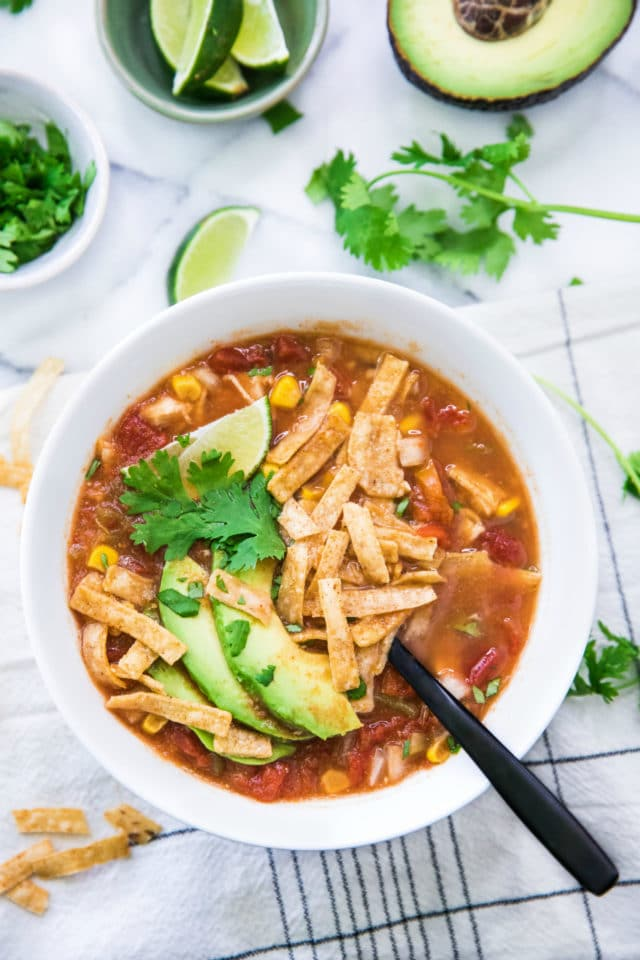 tortilla soup with avocado, tortilla strips, lime and cilantro