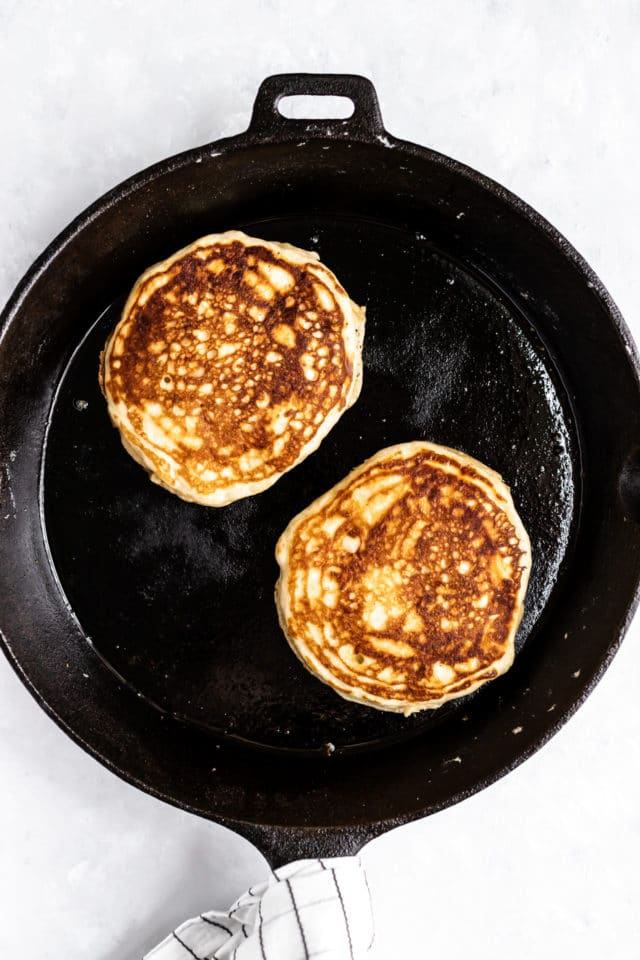 Buttermilk Pancakes cooking in an iron skillet