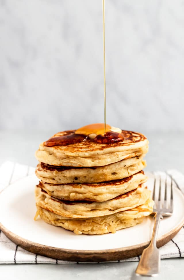 a stack of Buttermilk Pancakes topped with butter and dripping maple syrup