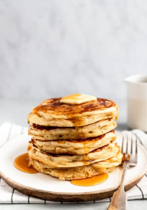 a stack of Buttermilk Pancakes served on a white plate with butter and maple syrup