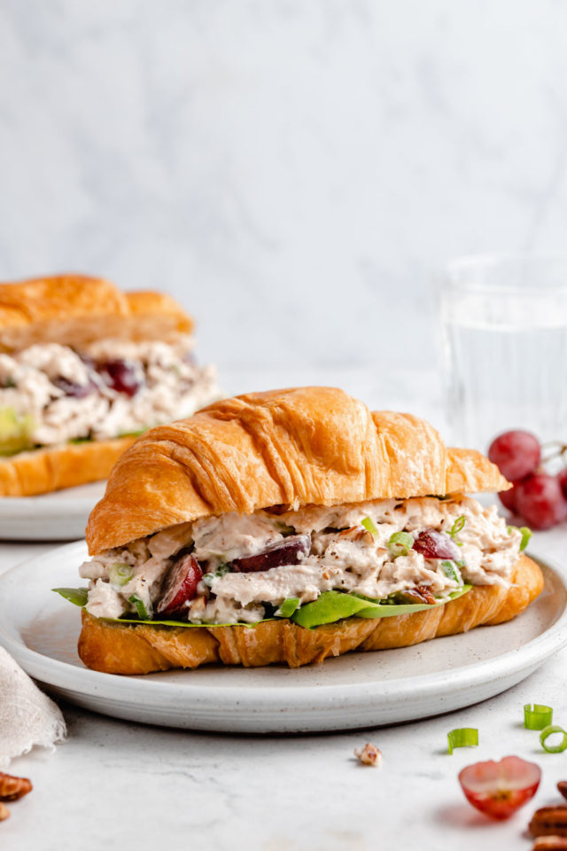 chicken salad sandwich with grapes and rotisserie chicken on a croissant