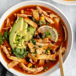 crockpot chicken tortilla soup topped with tortilla strips, avocado slices and lime