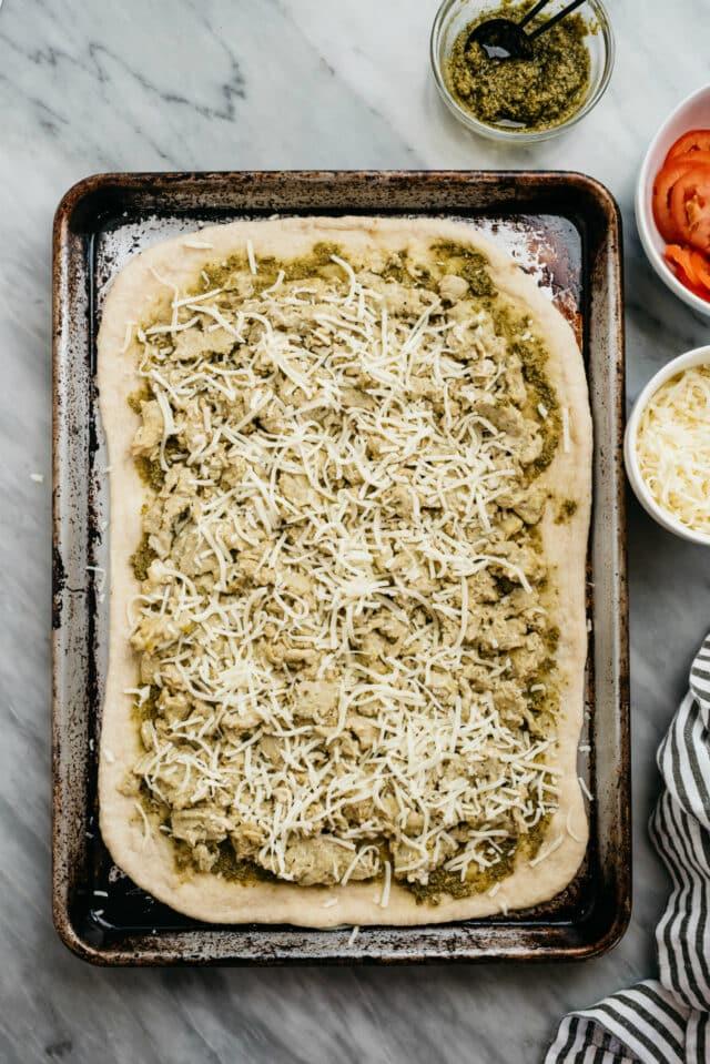 making Breakfast Pizza with pesto, scrambled egg and mozzarella