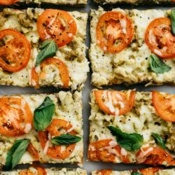 pizza with tomatoes and basil cut into squares