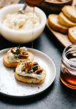 drizzling honey on goat cheese crostini