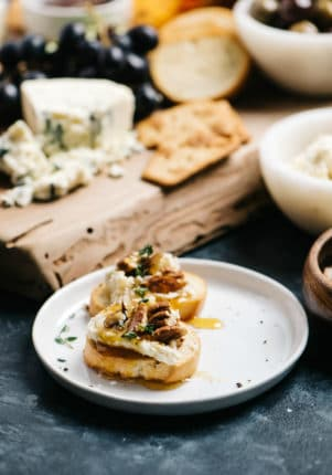 little toasts topped with goat cheese, honey and pecans served near a cheese board