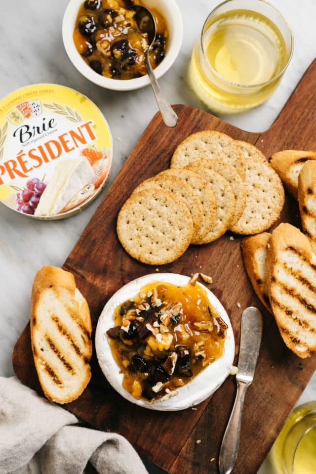 brie topped with jam and nuts and served with crackers and toast