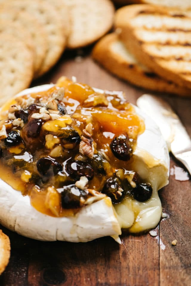 baked brie topped with jelly and nuts