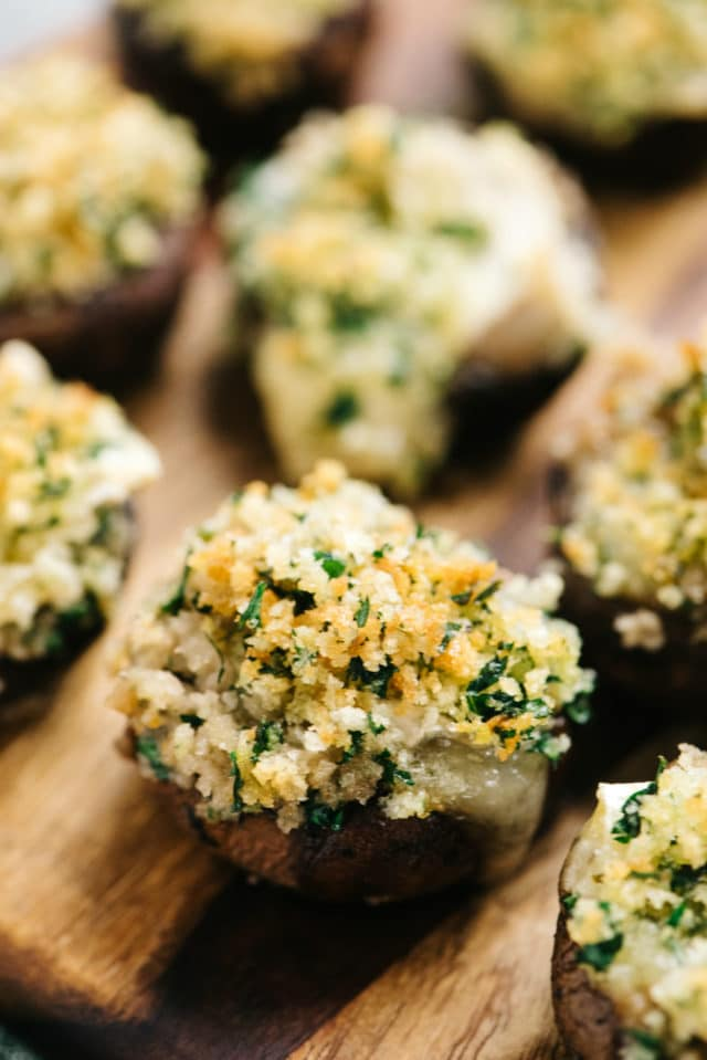 brie stuffed mushrooms on a wooden serving plate
