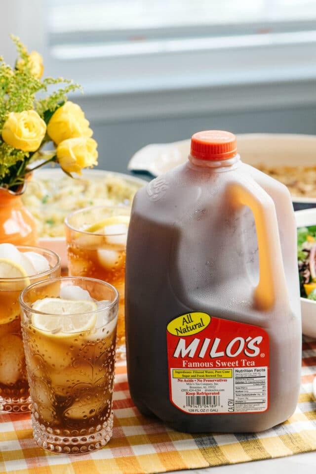 Milo's gallon jug of tea sitting near glasses filled with ice and tea