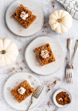 Pumpkin Bars on white plates sitting near little white pumpkins
