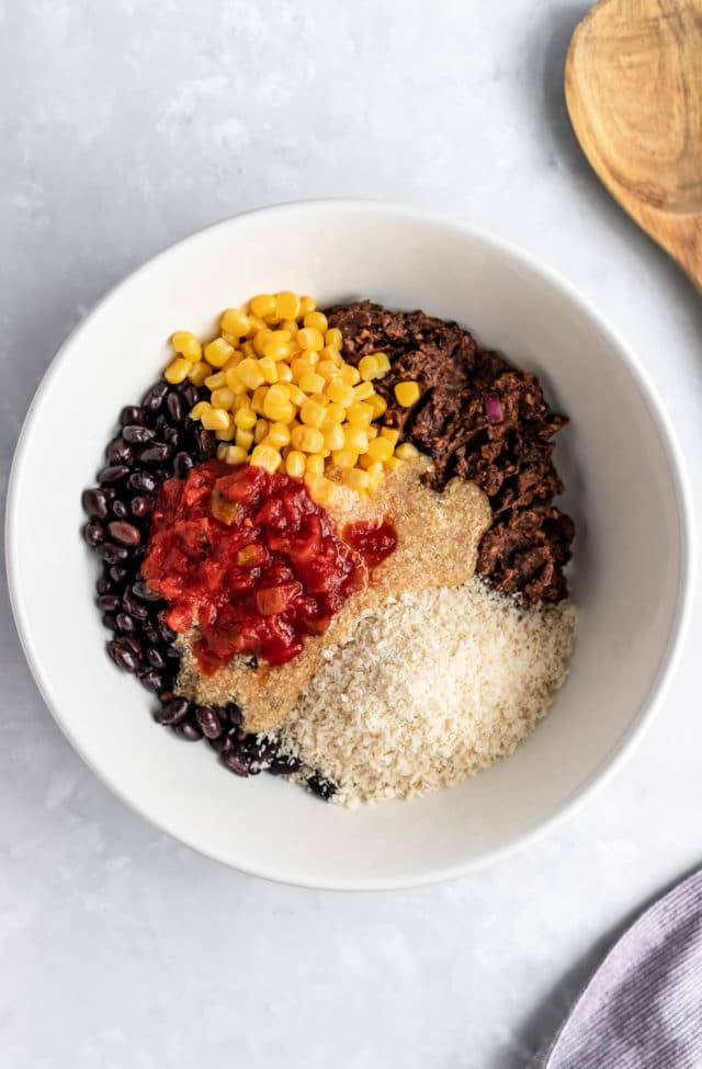 mixing black bean burger ingredients in a large white mixing bowl