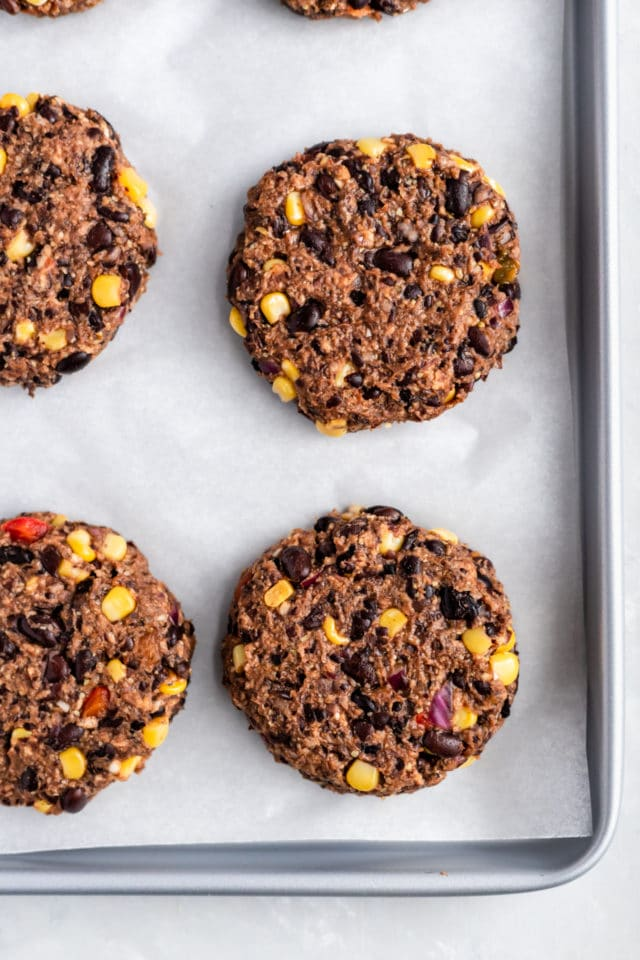 black bean burgers with corn formed into patties on parchment paper