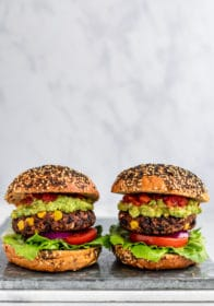 two of the best plant-based burgers topped with guacamole, tomato and lettuce