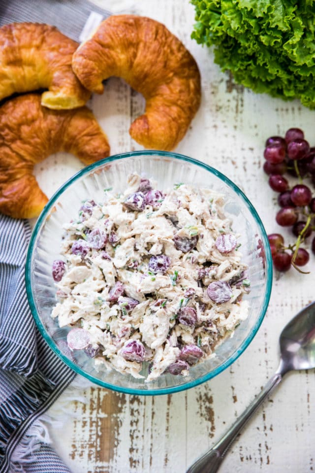 a glass mixing bowl filled with chicken salad with croissants and red grapes nearby