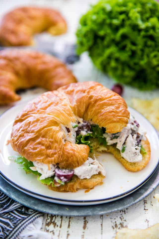 chicken salad on a croissant served on a white plate
